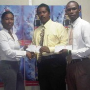 Ms Melinda Telesford presenting cheques to Timon Thomas of WHSS and Lester Blache of SAASS