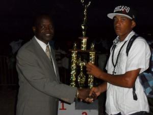 Minister Nimrod presents winning trophy to HSS athlete Uriah Enoe