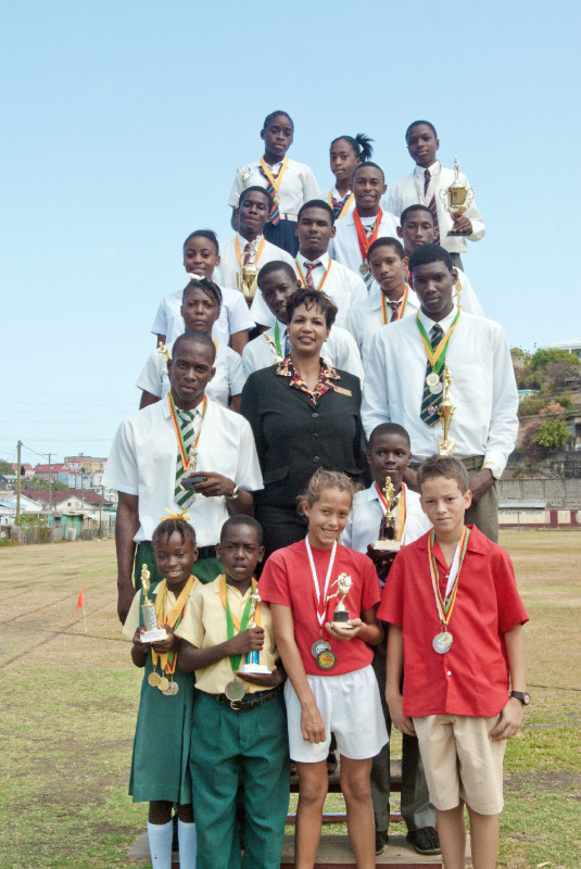 Winners podium showing CARIFTA athletes and winners from other schools with CIBC FirstCaribbean representative, Marlene Lander