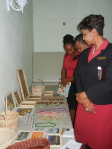 CIBC FirstCaribbean representative and guests viewing and purchasing craft made by persons with disabilities