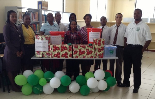 Mrs. Ann David-Antoine of the MOH flanked by teachers and students of the GBSS - on display infront are the items donated to the General Hospital