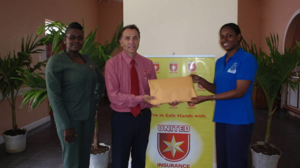 Mrs Marlene Finley receives travel insurance documents from Trevor Renwick & Donna Matthew of United Insurance