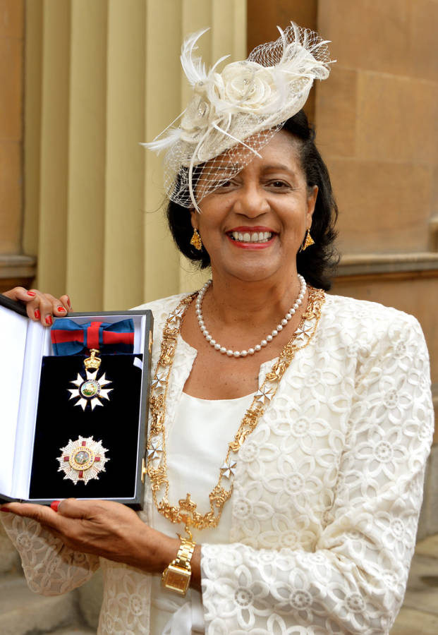 Governor General of Grenada Dame Cécile La Grenade holds up her Insignia of the Distinguished Order of Saint Michael and Saint George Dame Grand Gross after it was presented to her by The Prince of Wales at an Investiture ceremony at Buckingham Palace, 11 July 2014.