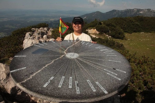 Suelin and Grenada's flag at Mount Gradišče, the summit of Velika Planina at 5466 feet. Photo Lojze Kalinsek