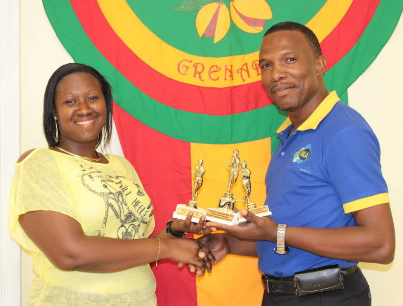 NLA's Marketing & Business Development Assistant – Mr Amilcar George handing over Trophies to Representative from St Peter's RC School