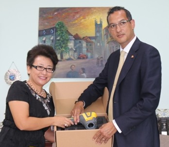 Health Minister Nickolas Steele receives items from Madam Ou Boqian, resident Chinese Ambassador to Grenada.