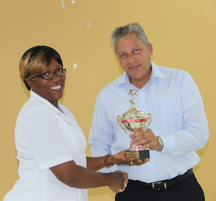 Trevor Noel - Asst. Dir. WINDREF presenting the award for the Highest Immunization Coverage