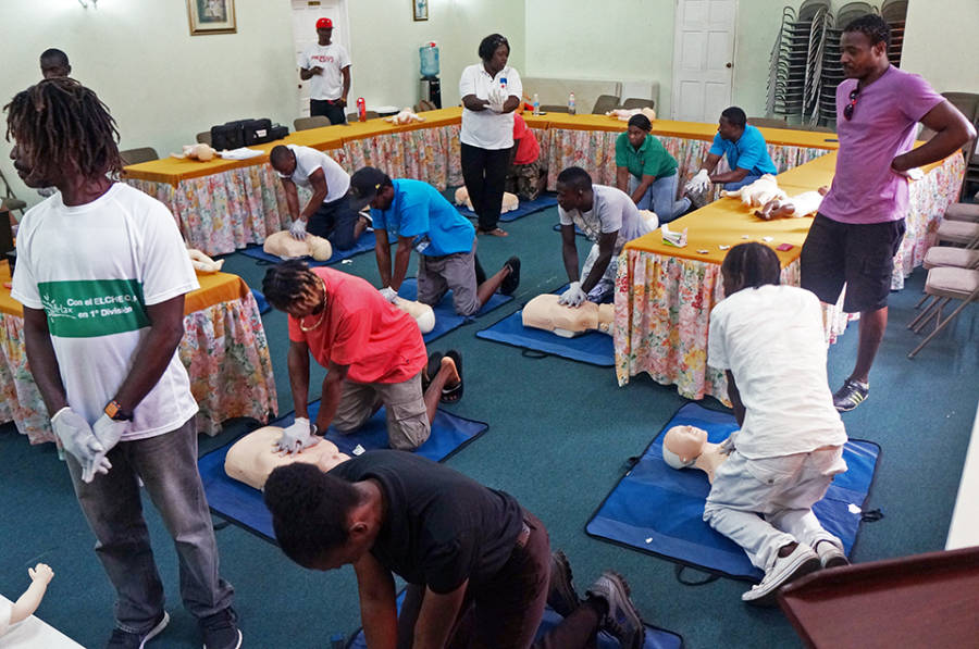 Water-sports operators practice chest compressions for CPR on dummies