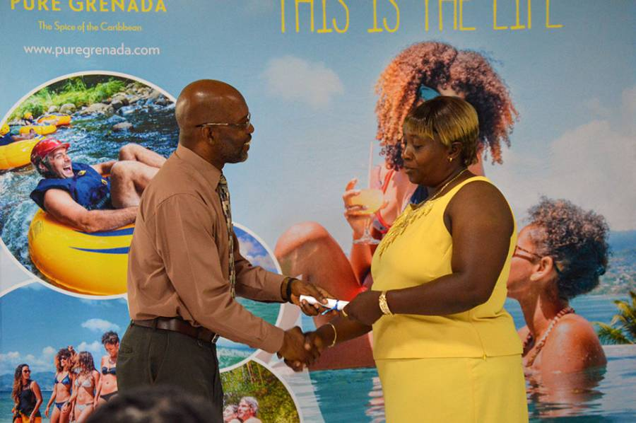 4Sep2015---Mr.-Lincoln-Morgan,-CEO-of-the-GNTA-hands-a-certificate-to-a-Grand-Anse-beach-salesperson