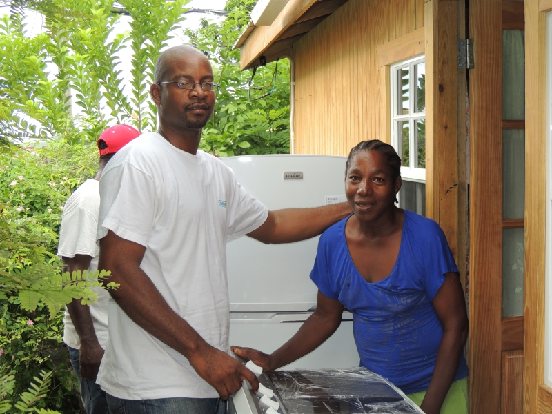 FastCash Country Manager Stephen Joseph presents appliances to LeslieAnn Francois