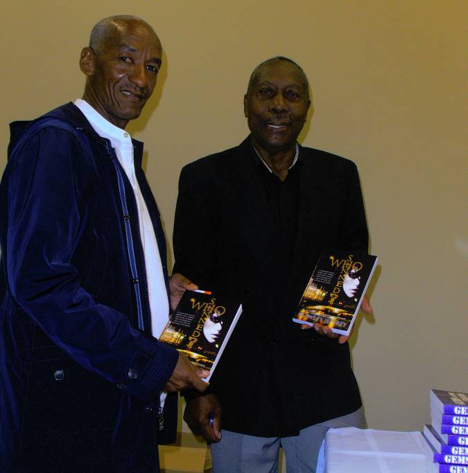 Rowley Jeffrey (right) after autographing a copy of his book for visiting Grenadian George Robinson, a former national track athlete
