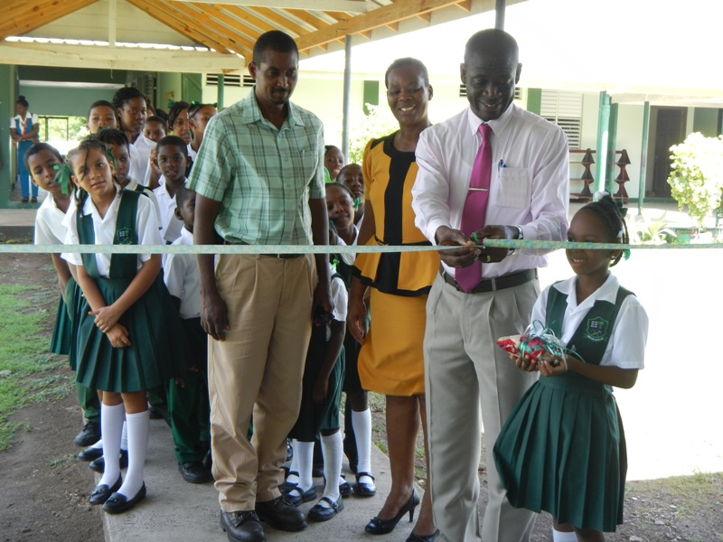 GRENLEC's Branch Manager Wallace Collins cuts ribbon as  his colleague Floyd Best, Principal Barbara Charles and students lo