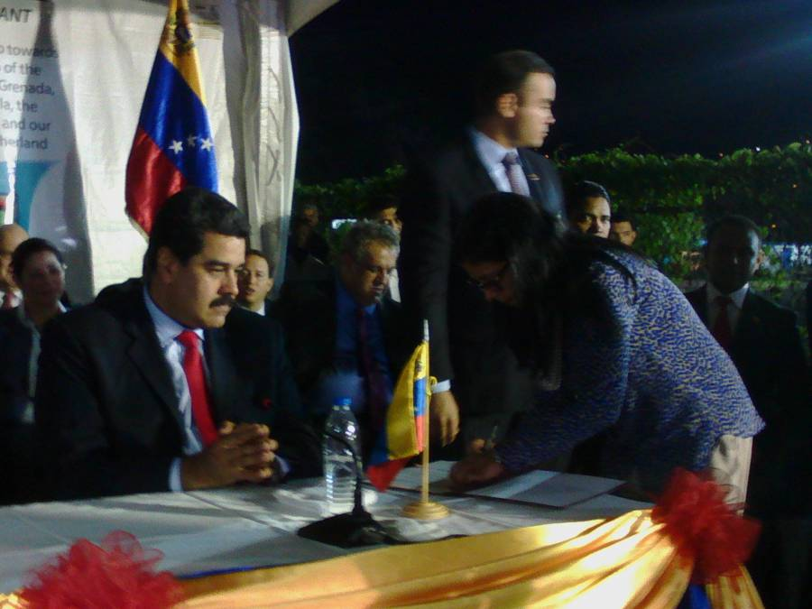 Maduro watching while his minister signs the miracle eyes programme agreement