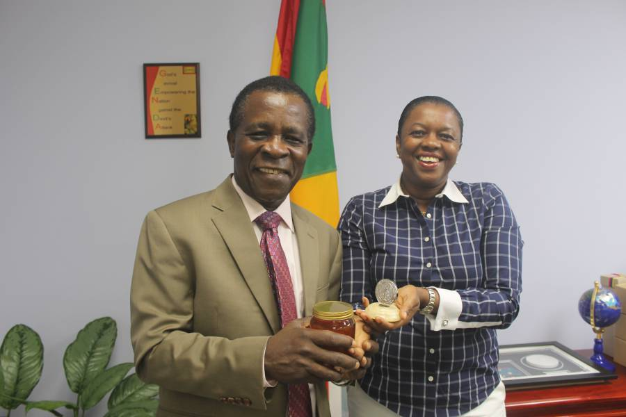 "Prime Minister Dr. the Right Honourable Keith Mitchell, as he was presented with dozens of jars of the award-winning honey by Dr. Valma Jessamy, who is herself holding the Medal of Ukraine which the team won for the ""best honey in the world."""