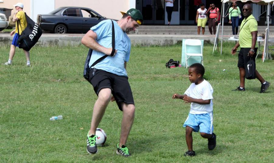 JRF Team Member and child playing soccer