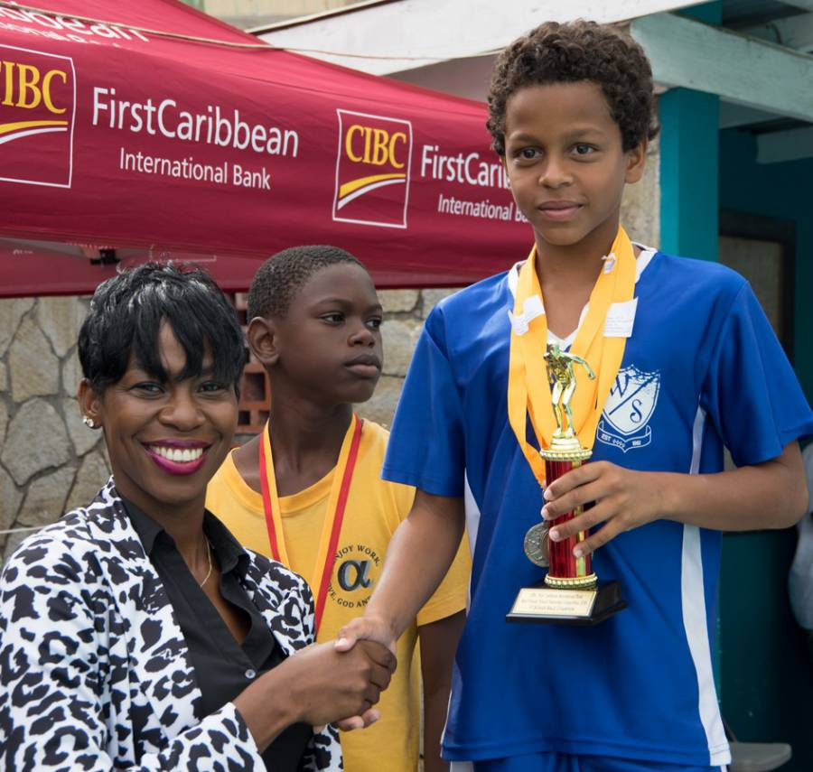 CIBC FirstCaribbean Grand Anse Branch Manager Matonia James Presents Trophy to Zackary Gresham the Top Placing Male Swimmer