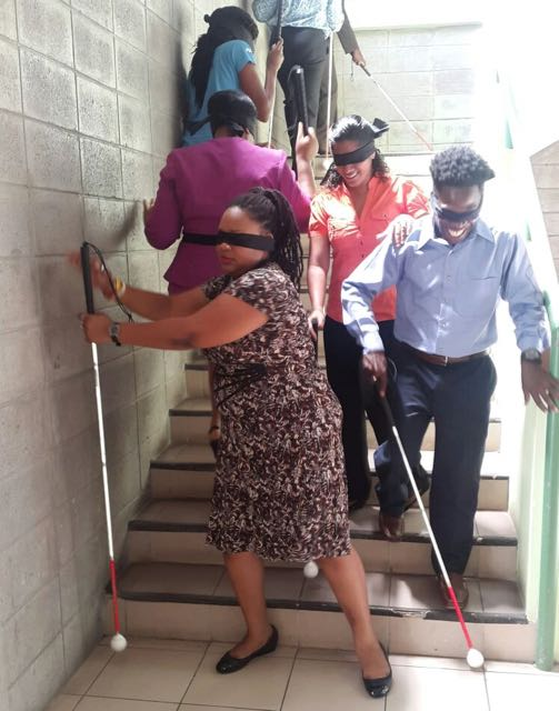 Blindfolded media workers attempt to navigate their surroundings