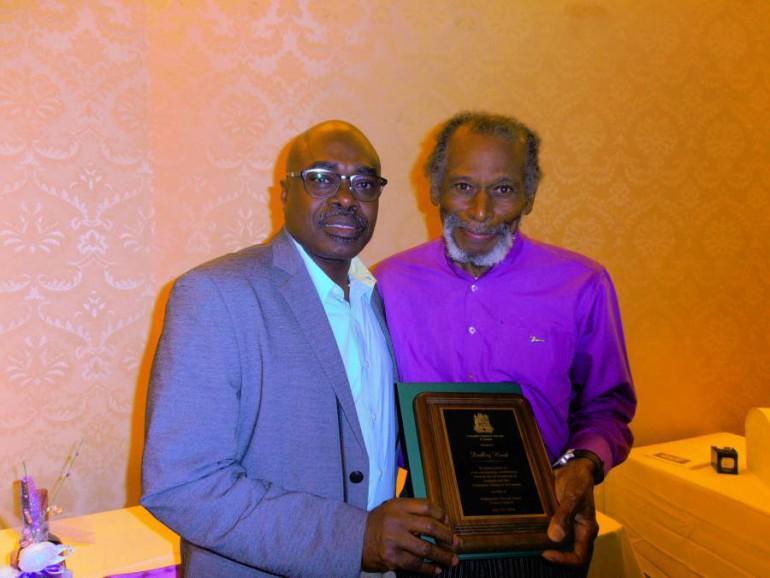 Ambassador James left presenting plaque to Dudley Hood