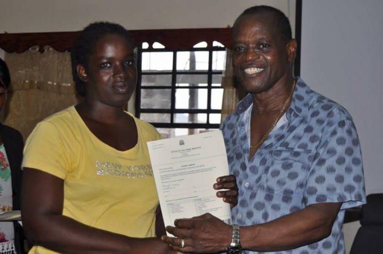 Minister Nimrod handing over School Uniform Voucher to a recipient.