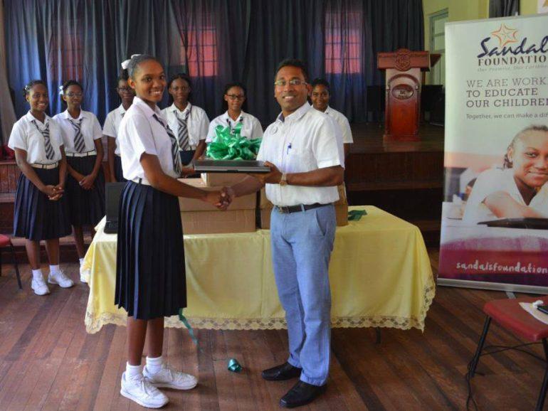 Hotel Manager, Supratik Guha handing laptop to student, Shanique  Emmanuel